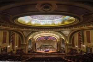 An interior view of the seating, stage, and large painted ceiling.