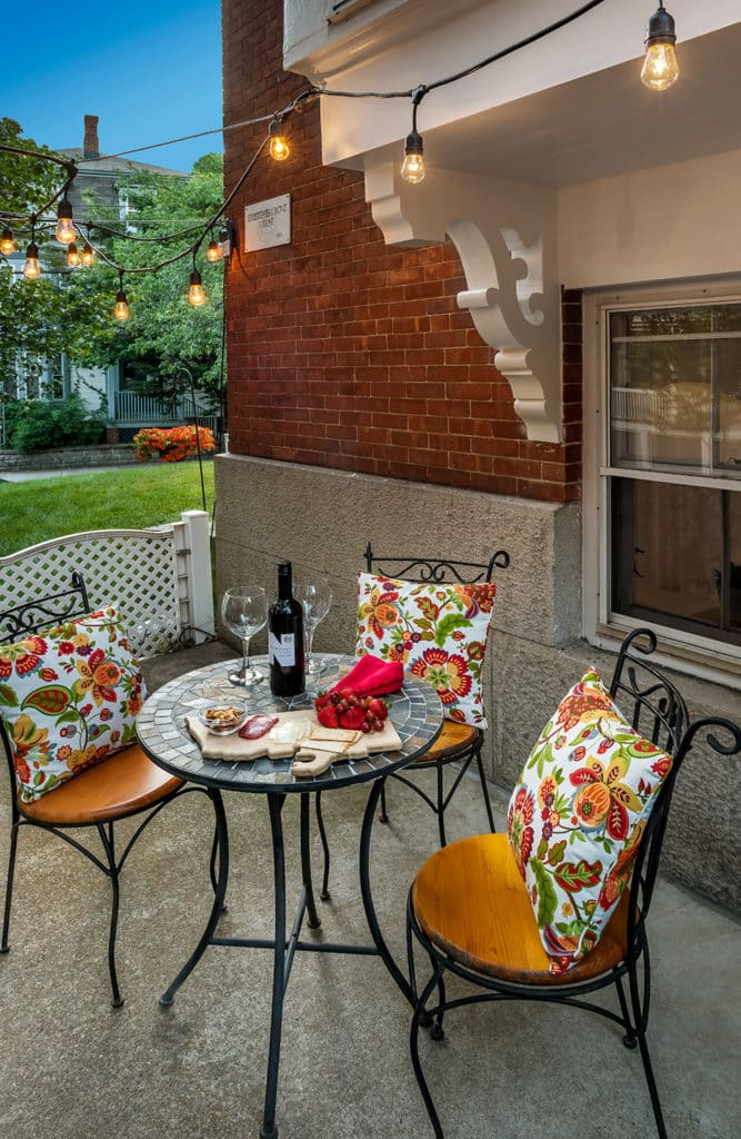 Patio table featuring a bottle of red wine and a charcuterie board.