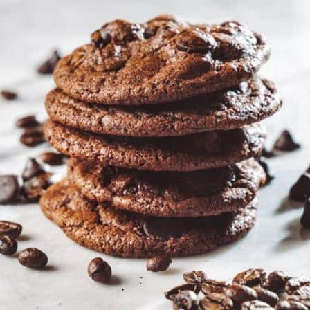 A stack of 5 chocolate espresso cookies with choclate morsels sprinkled around them.