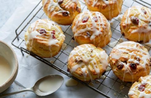 Buttery cranberry orange scones drizlled with icing placed on a cooling rack.