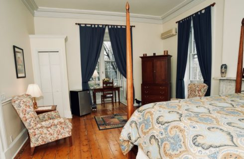 Spacious guest-room with original wooden floors and a four post bed with a blue and tan cover and a wooden armoire.