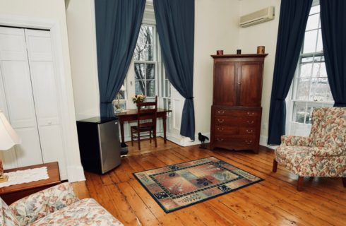Room with large window with blue drapes, a wooden armoire, mini-fridge and desk.