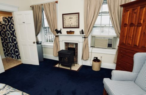Guest-room with a wood stove, blue patterned wing chair, wooden armoire, and blue wall-to-wall carpeting.