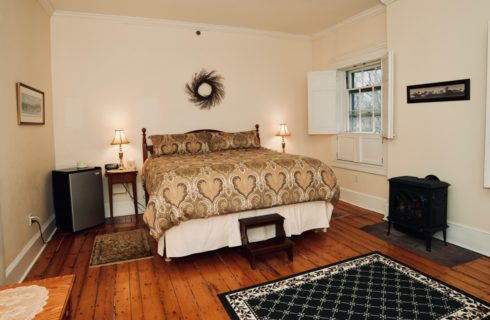 King bed in bedroom with windows with shutters and a patterned area rug over original hardwood floors.