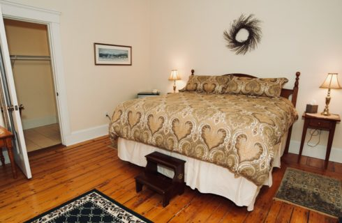 King bed in room with original hardwood floor and two tables with lamps.