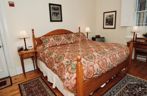 Large four post bed in a bright patterned comforter with two nightstands holding lamps.