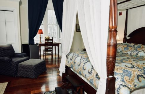 Wooden canopy bed in a bedroom with a blue chair and ottoman and a desk under a large window.