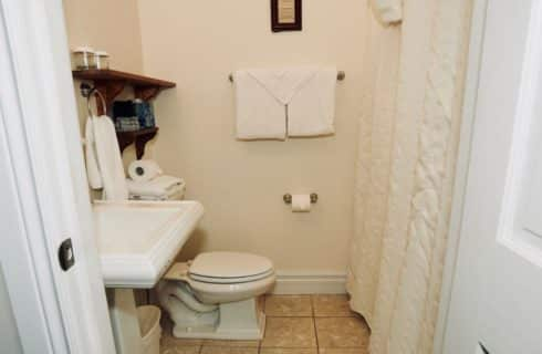 Bathroom with white pedestal sink, stool and white shower curtain.