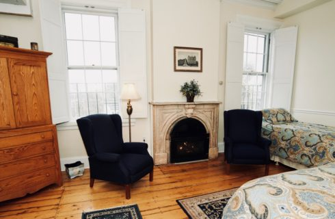 Spacious room with a fireplace, wooden armoire, two blue wingback chairs, and a king and twin bed.