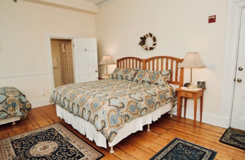 Large bright room with a wooden king bed and twin with blue patterned coverings, night stands with lamps, and original hardwood floors.