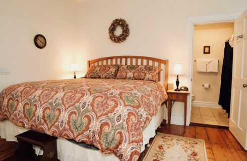 Large king sized bed made up with a bright patterned spread with two night tables and lamps in a room with cream walls.