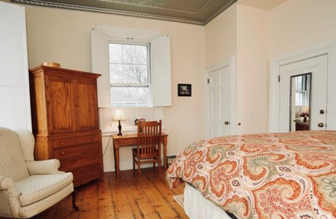 Guest room with original hardwood floors, a wood desk and armoire, and a cream wingback chair all facing a king bed.
