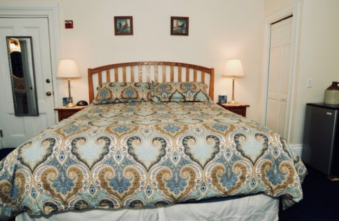 A king bed made up in a blue covering, 2 nightstands with lamps, and a small refrigerator.