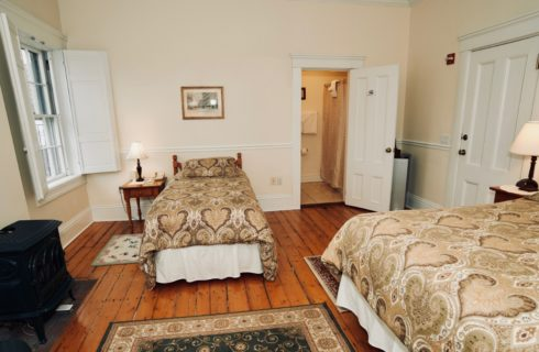 Large bright room with a king and a twin bed facing shuttered windows and a wood stove