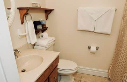 Bathroom painted white linen with a wooden vanity, a toilet, and a gold shower curtain.