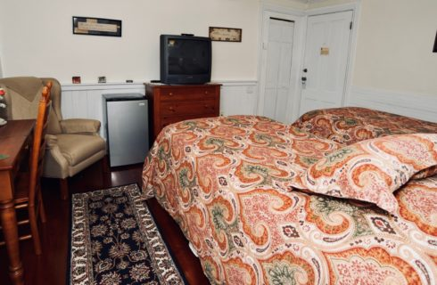 A cozy room featuring two twin beds made up in red patterned comforters, a wooden desk with a tv, a beige wingback chair, wooden desk, and small refrigerator.