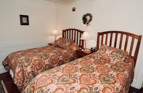 A cozy room featuring two twin beds made up in red patterned comforters featuring two end tables with lamps.