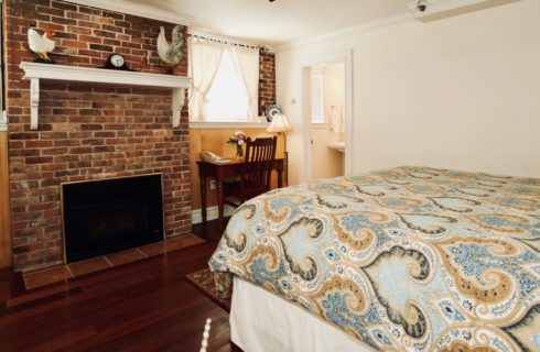 King bed with paisley blue comforter in a room with a brick fireplace and a wooden desk.