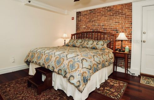 King bed with paisley blue comforter, two night stands with lamps, and a brick accent wall.
