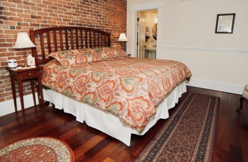 King bed made up in a paisley bedspread with two end tables with lamps in a room with hardwood floors.