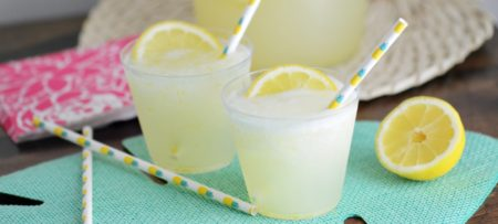 Two small clear plastic cups filled with frozen lemonade and a slice of lemon with a straw.