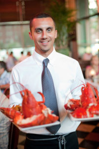 A gentleman waiter holding to plates of large cooked red lobsters.