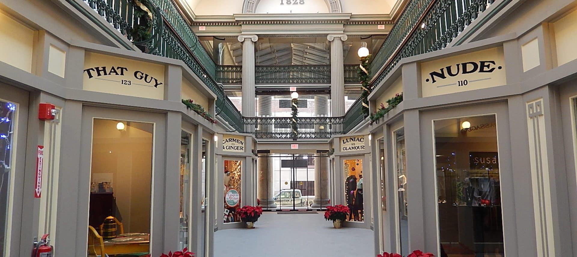 An indoor shopping mall corridor lined with holiday poinsettias.