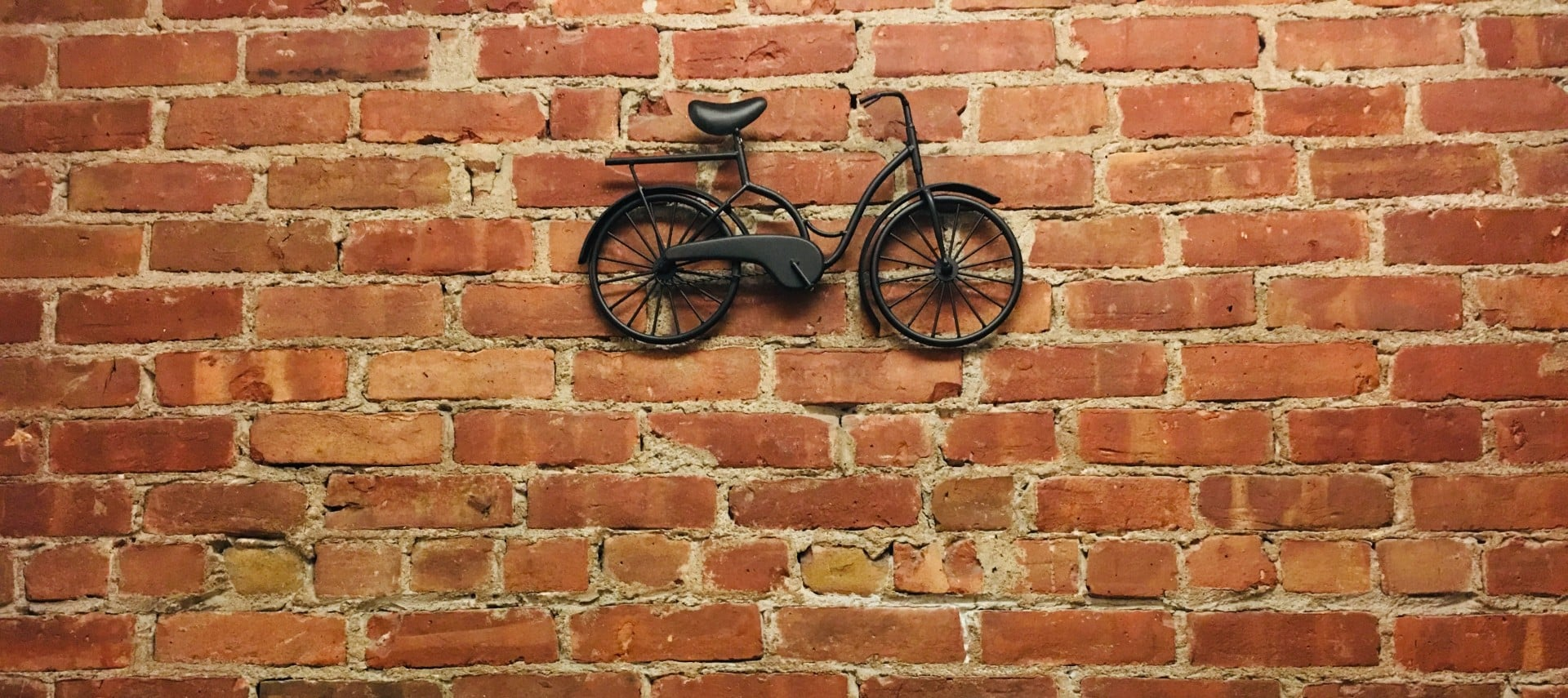 Red brick wall with a black metal bike.