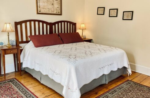 A King bed made up in cream quilt and red shams with nightstands and lamps.