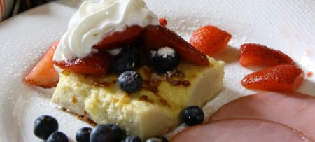 Finnish Pancake topped with fresh berries and whipped cream on a white plate.