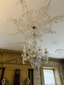 A large glass candle light chandelier hanging from a beautiful plaster ceiling.