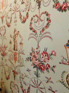 Vintage light blue wallpaper with a pink floral design.