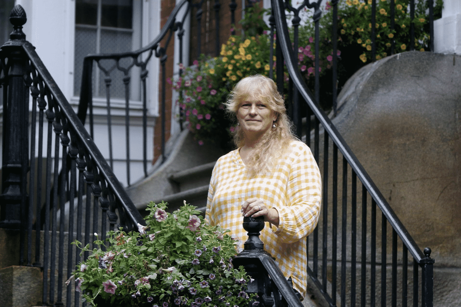 A woman wearing a yellow plaid top standing next to a beautiful flower box attached to a black iron railing.