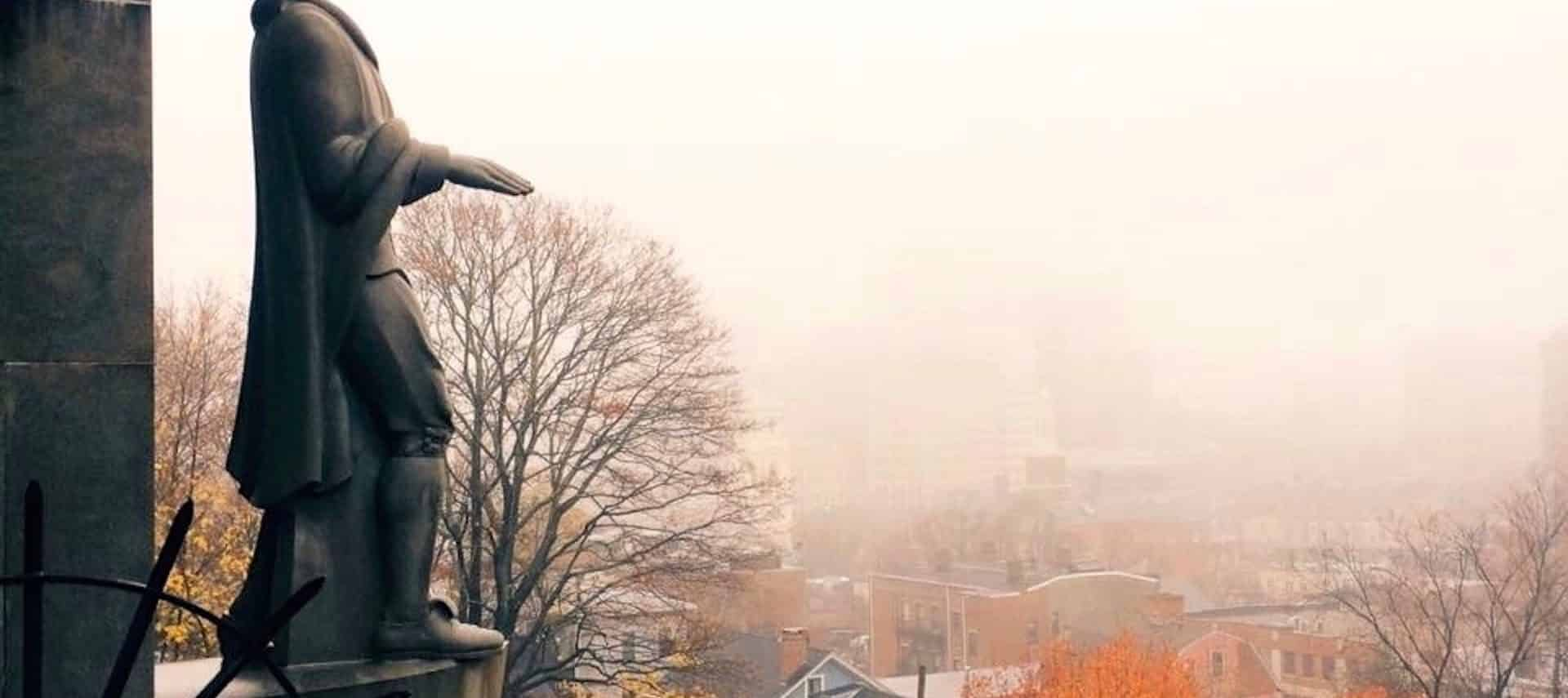 A large statue of Roger Williams situated on a hill overlooking Providence on a foggy fall day.