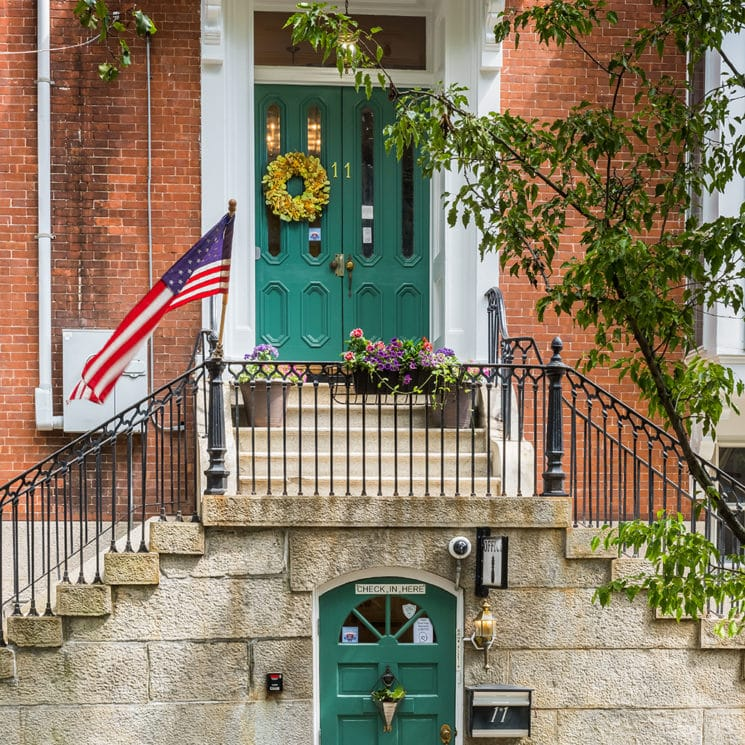 Our main entryway with green double doors and a spring wreath.
