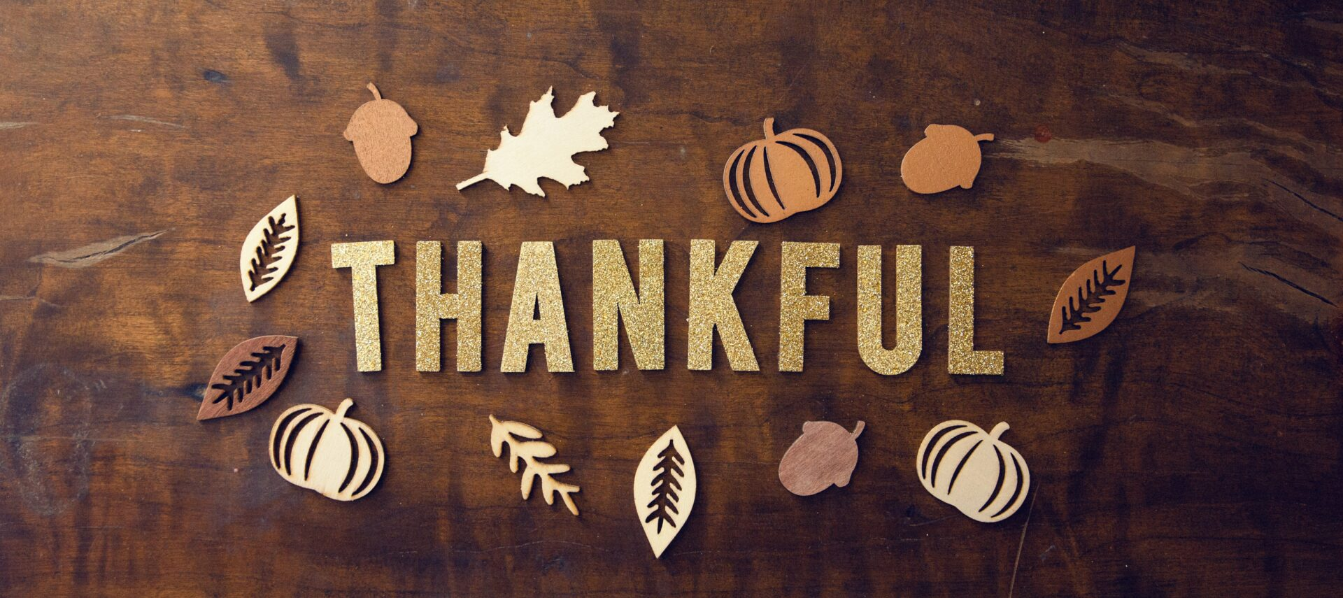 Wooden table with decorative gold leaves and the word thankful spelled out.