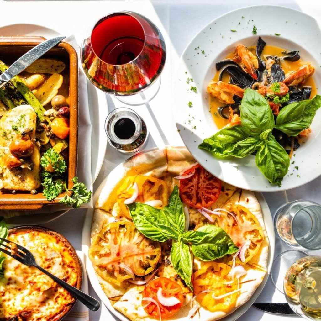A delicious spread of Italian dishes of food with a glass of red wine.