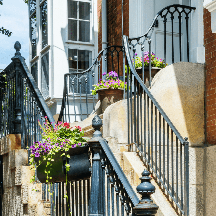 Bright beautiful flower boxes hanging on a black railing outside.