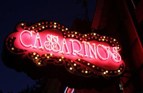 A red neon sign glows in the dark with the word Cassarino's