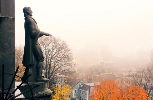 A statue a a colonial man looks over a town covered in fall foliage on a misty morning.