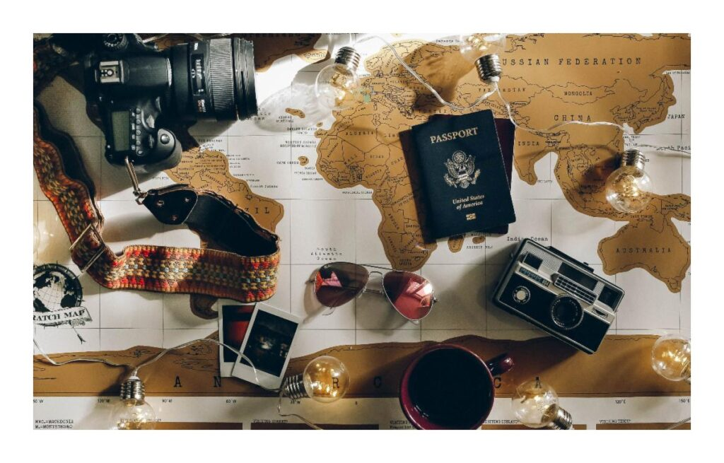 A world map spread out with a camera, film, and passports on top.