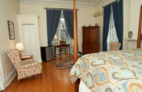 Spacious guestroom with wooden floors and a four post bed with a blue and tan cover and a wooden armoire.