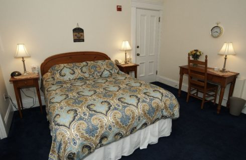 Guestroom with queen bed with a blue and tan comforter with two nightstands and a wooden desk.