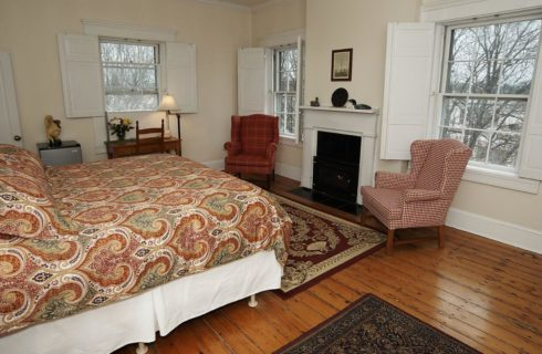 Bedroomw ith king bed and a fireplace surrounded by two rose wingback chairs and a wooden desk.