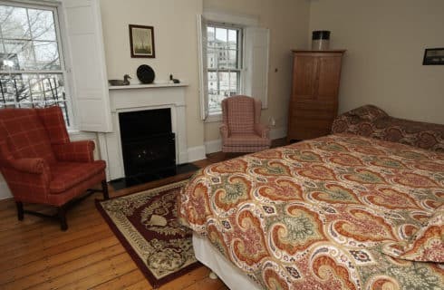 King bed in orange faces a white fireplace and w wooden armoire with two wing back chairs.