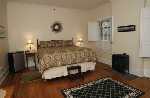 King bed in bedroomw ith windows with shutters and a patterned carpet.