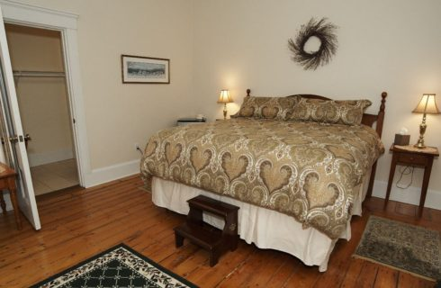 King bed in room with wooden floor and two tables with lamps.