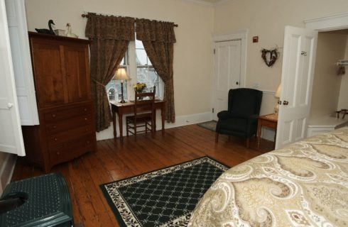 King bed in room with wood floor, armoire, chair and wood burning stove.