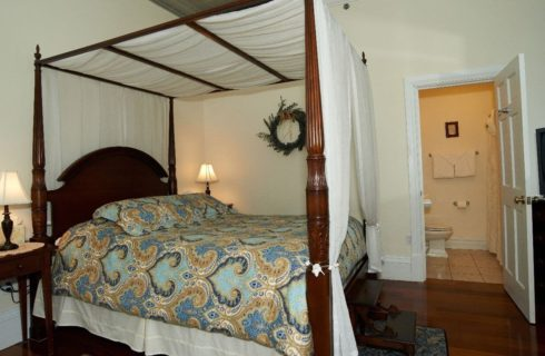 Queen bed canopied in white with a blue patterned comforter.