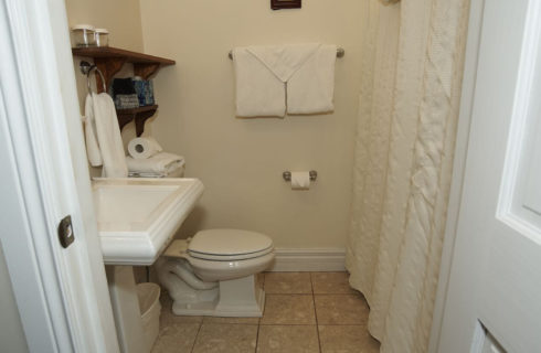 Bathroomw ith white pedestal sink, stool and white shower curtain.